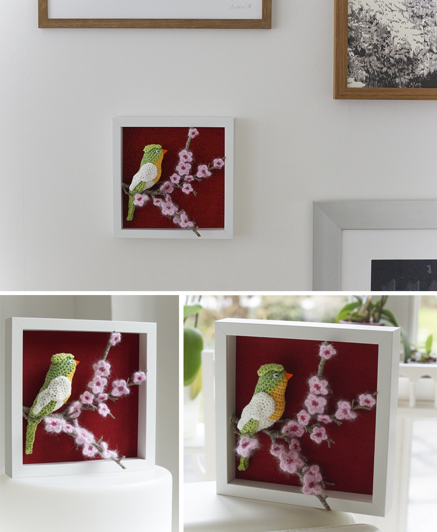 gehaekelter vogel auf kirschbluetenast in dekorahmen